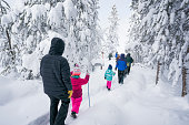 Wyoming, USA - February 20, 2018: Tourists follow a gude on a snowy trail through a frosty forest in Norris Geyser Basin to visit Yellowstone's hottest hydrothermal area during winter on a snow coach excursion from Mammoth Hot Springs Hotel in Yellowstone National Park