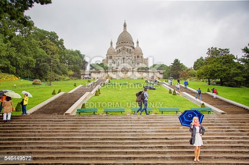 Paris, France - September 9, 2013: Tourists visiting Paris Sacre-coeur basilica during rainstorm, most under an umbrella. A female is posing for an unseen photographer at the bottom of the steps.