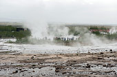 Strokkur geyser, Iceland - MAY 20, 2019: Tourists visiting and waiting for the eruption of Strokkur geyser in the Golden Circle of Iceland