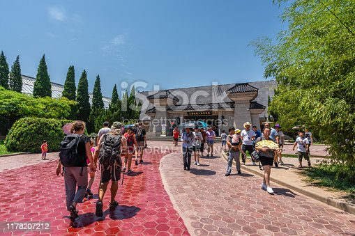 Xian, China -  July 2019 : Tourists walking on a path road leading to a museum site building containing Terracota Army sculptures, Xian, Shaanxi Province