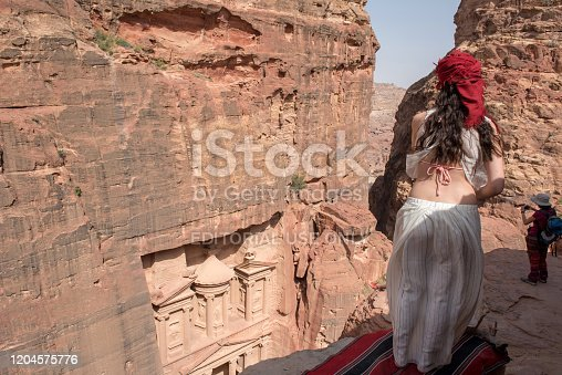 PETRA, JORDAN - MAY 18, 2018: Traveler woman looking down to the archeological site of the Treasury, Petra, part of Unesco Heritage