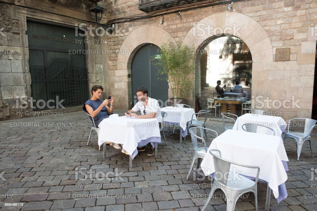 Tourists wait for lunch in Felip Neri Plaza in Barcelona stock photo