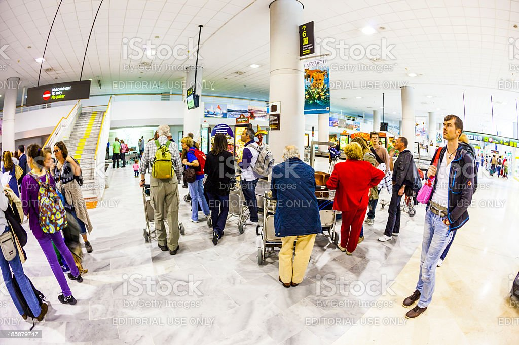 tourists wait for their baggage at the airport stock photo