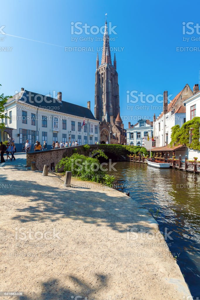 BRUGES, BELGIUM - APRIL 6, 2008: Tourists walk across Dijver canal in front of Church of Our Lady stock photo
