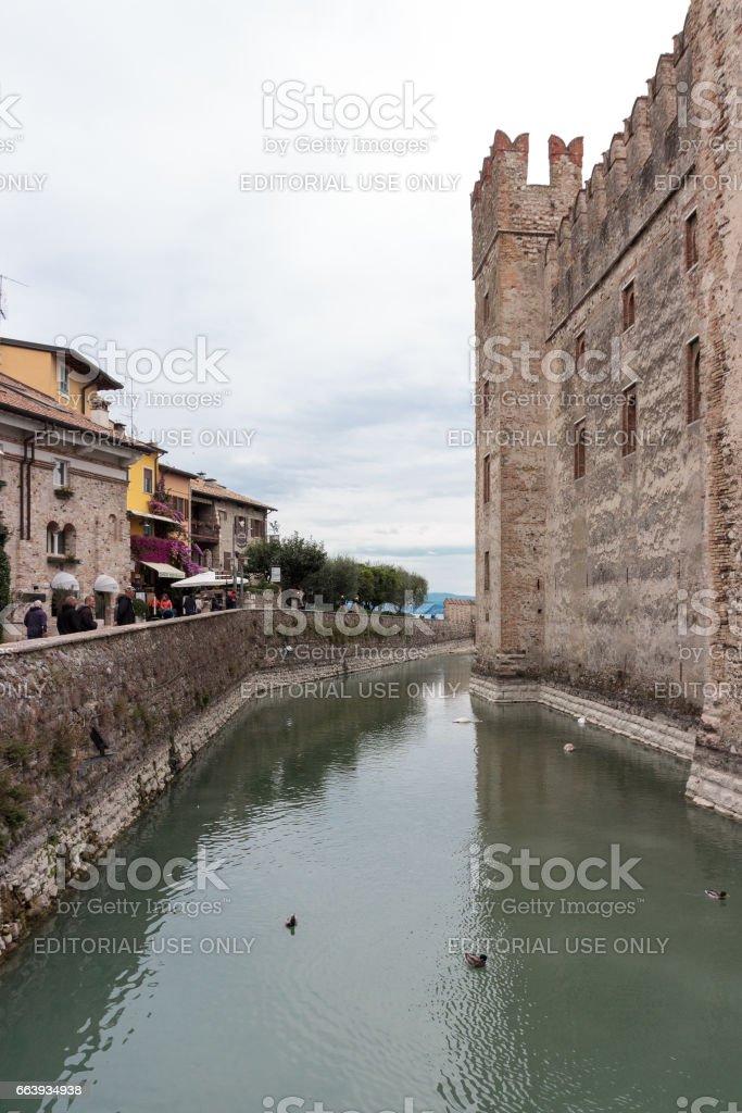 Tourists walk along embankment near Castello Scaligero wall in Sirmione stock photo