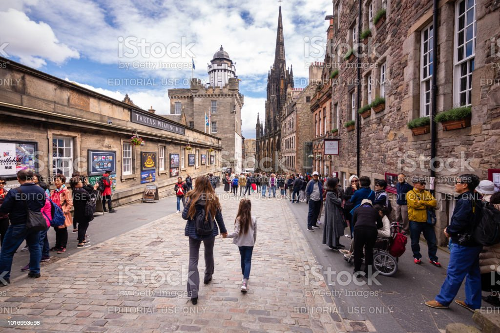 Tourists walk along the Royal Mile near Edinburgh Castle stock photo