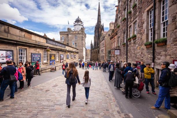 Tourists walk along the Royal Mile near Edinburgh Castle stock photo