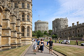 Windsor, England, UK - July 7, 2017:  Tourist walk along St George's Chapel on their way to the entranceway with Windsor Castle in the background.
