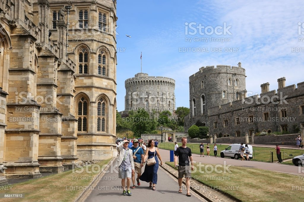 Tourists walk by St. George's Chapel in Windsor Castle, UK stock photo