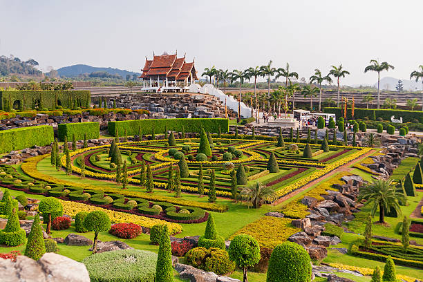 Tourists walk in Nong Nooch Tropical Garden in Pattaya, Thailand. stock photo