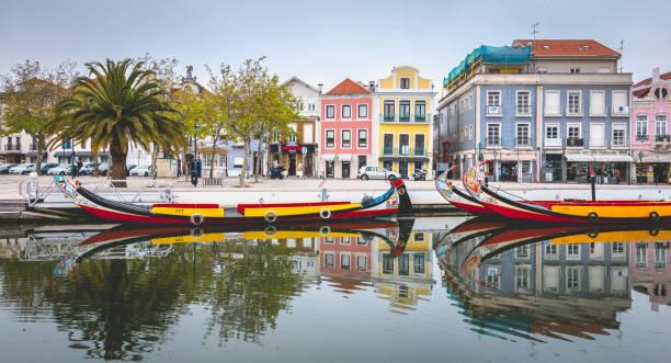 tourists walk on famous moliceiros of aveiro in portugal - aveiro imagens e fotografias de stock