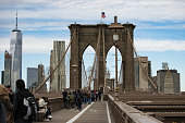 Tourists walk on the famous Brooklyn Bridge in Manhattan, New York, United States. The Brooklyn Bridge is a hybrid cable-stayed/suspension bridge in New York City. It connects the boroughs of Manhattan and Brooklyn, spanning the East River.