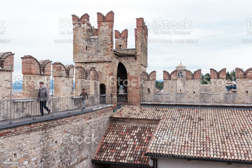Tourists walk on the walls of Castello Scaligero in Sirmione stock photo