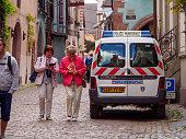 Tourists walk past police van, Riquewihr, France