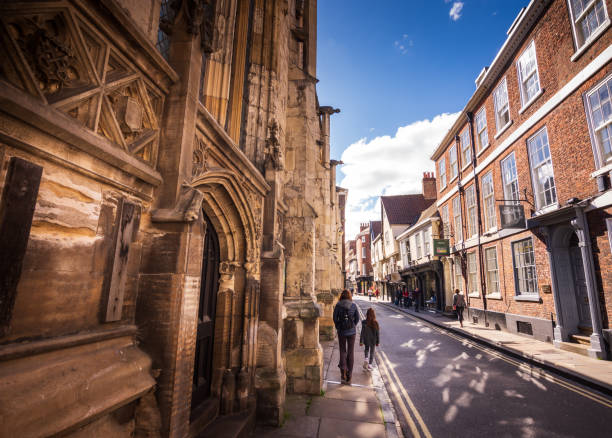 Tourists walk past the York Minster Cathedral in York, UK stock photo
