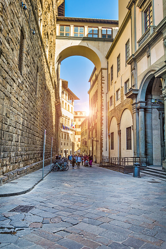 FLORENCE, ITALY - MAY 13,2019: Tourists walk through the picturesque streets of Florence on a bright sunny day