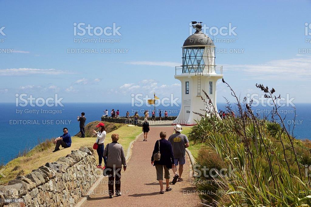 Tourists walk toward lighthouse at Cape Reinga, Northland, New Zealand stock photo
