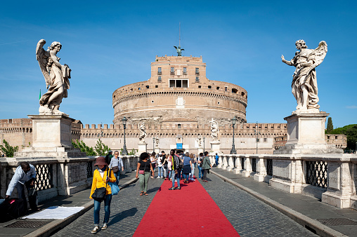 Rome, Italy - October 2019: Tourists walking across the bridge to Castel Sant'Angelo (Castle of the Holy Angel) or The Mausoleum of Hadrian, a mausoleum for the Roman Emperor Hadrian, fortress and castle, now the museum in Rome, Italy