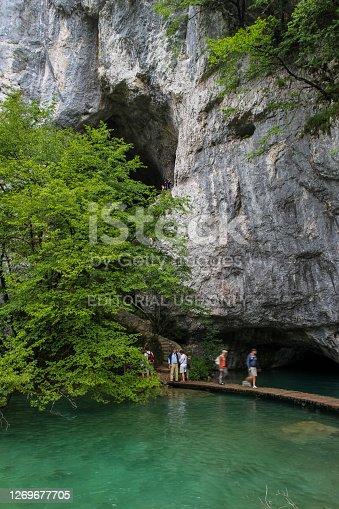 Plitvice Lakes, Croatia - July 14th 2018: Tourists walking along a raised path, through a large cave, on Plitvice Lakes, Croatia