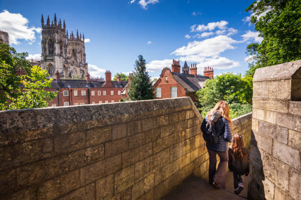 Tourists walking along York's city walls in England stock photo