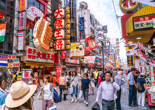 Tourists walking around crowded Osaka Dotonbori entertainment district