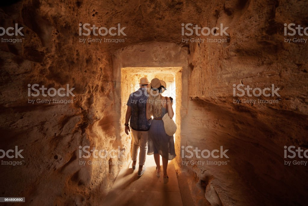Tourists walking in dark passage at archaeological site in Greece royalty-free stock photo
