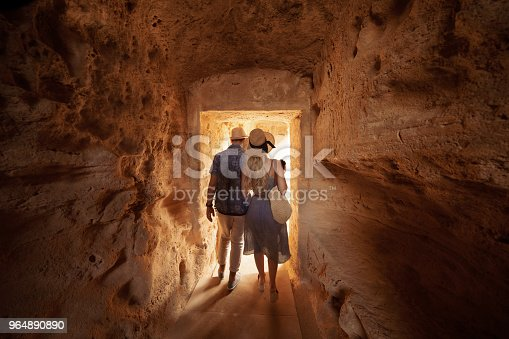 Tourists walking in tunnel and doing sightseeing at ancient archaeological tombs site in Italy