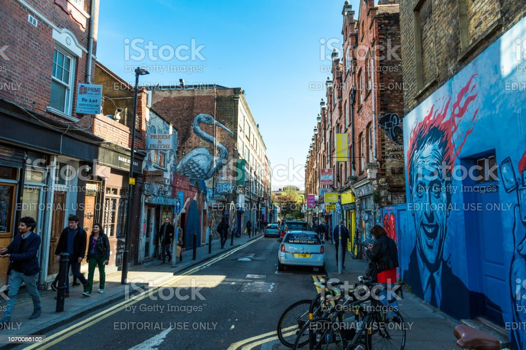 Tourists walking in the crowded street of Brick Lane, London, UK London, UK - 24 October, 2018: wide angle view of people walking on Brick Lane in east London, UK. It is a famous street known for its curry houses and restaurants, and for its Indian and Bangladeshi population. We can see lots of signs, some in neon lights, advertising the many restaurants and markets along the street. Room for copy space. Architecture Stock Photo