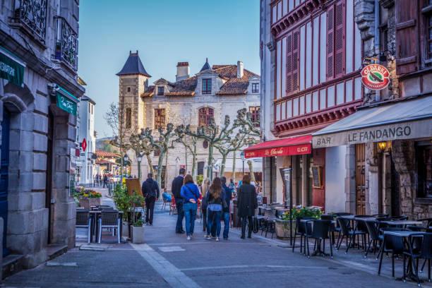 touristes à pied près de bar le fandango brasserie sur rue de la république, saint-jean-de-luz, france - république photos et images de collection
