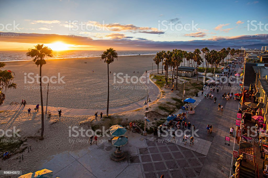 Tourists walking on footpath by beach during sunset stock photo