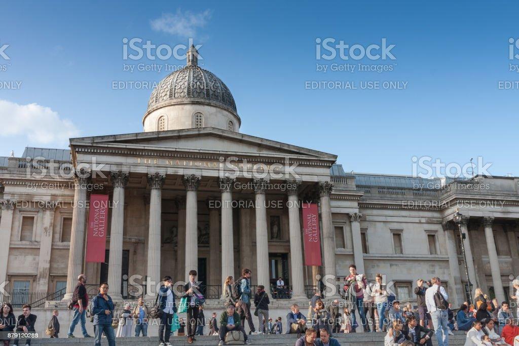 Tourists walking on Trafalgar Square, on background The National Gallery stock photo