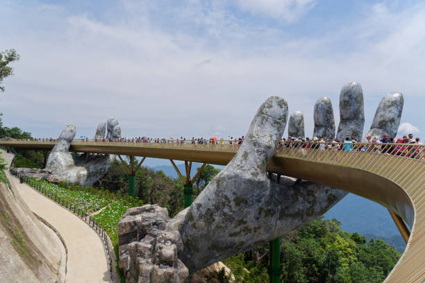 Tourists walking over the Golden Bridge lifted by two giant hands. Ba Na Hills mountain resort in Da Nang, Vietnam stock photo