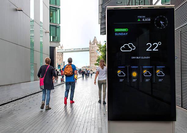 Tourists walking toward Tower Bridge, electronic display with weather forecast. stock photo