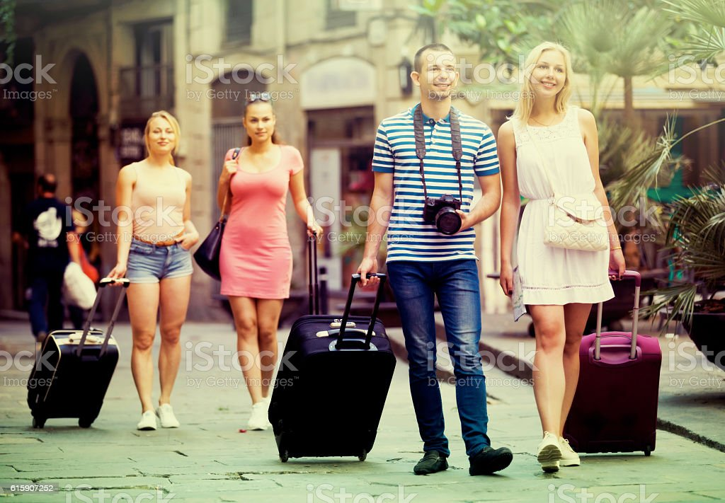 Tourists walking with suitcases stock photo