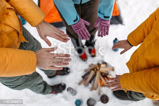 Three tourists warming hands by campfire on snow