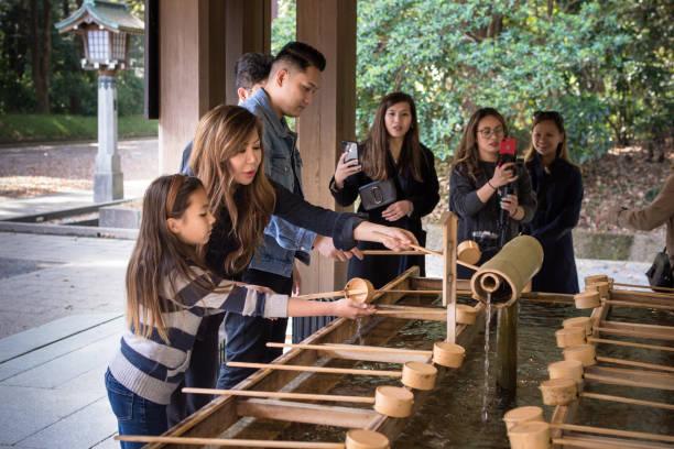 Tourists washing hands (Temizu) at Meiji-Jingu Shrine in Tokyo, Japan stock photo