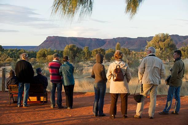 Tourists watch a sunset.