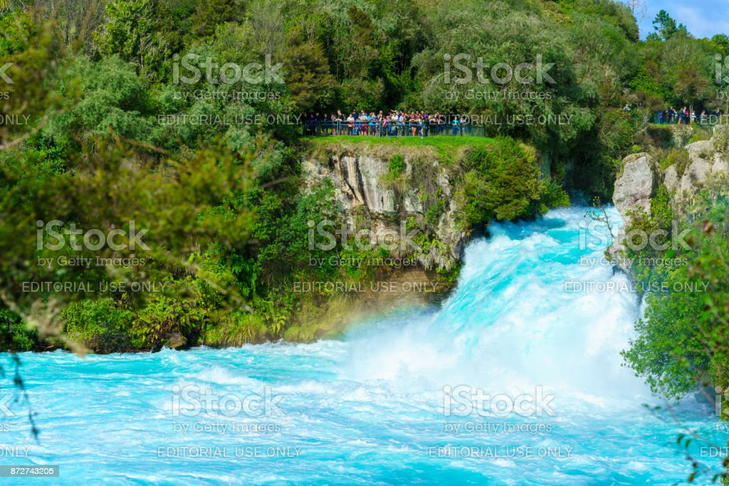 Tourists watching The Huka falls , the largest , fast and powerful waterfalls on the Waikato River , located in Wairakei Park of Taupo , North Island of New Zealand stock photo