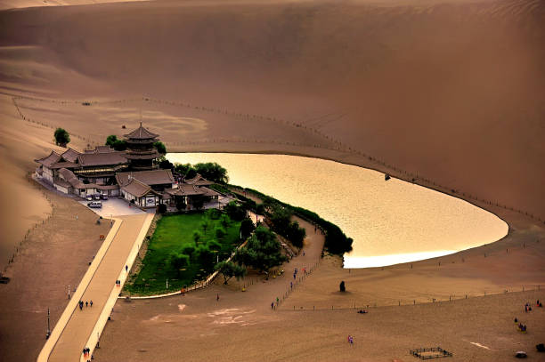 Tourists were visiting crescent lake, the oasis in the desert of Soughing Dunes (Mingshashan) in Dunhuang, Gansu, China Tourists were visiting crescent lake, the oasis in the desert of Soughing Dunes (Mingshashan) in Dunhuang, Gansu, China silk road stock pictures, royalty-free photos & images