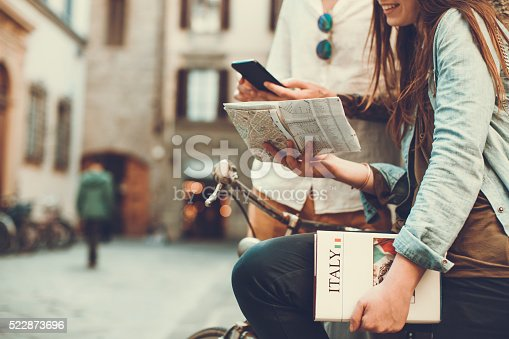 Tourists with guide and map in alleys of Italy. They sit on a bike in the small streets of Firenze.