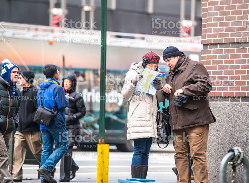 Tourists with NYC city map on Manhattan royalty-free stock photo