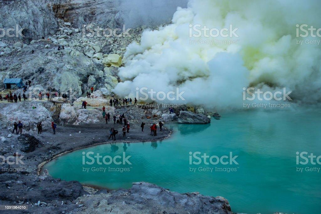 Turistas con humo de azufre en el volcán kawah ijen - foto de stock