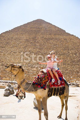 883177796istockphoto Tourists woman and girl are riding a camel in the background of the pyramids in Egypt 883177796