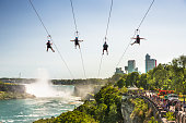 Niagara Falls: Tourists zip line over the Niagara River.  Niagara Falls is the collective name for three waterfalls that straddle the international border between Canada and the United States; more specifically, between the province of Ontario and the state of New York. They form the southern end of the Niagara Gorge.