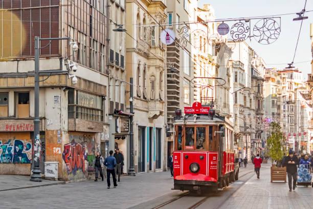toeristische rode nostalgische tram op istiklal straat tussen moderne en historische gebouwen met mensen en toeristen. - i̇stiklal caddesi stockfoto's en -beelden