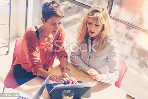 istock Tow beautiful businesswomen making conversation at modern studio office .Handsome coworkers at working process.Horizontal,blurred. 912682194