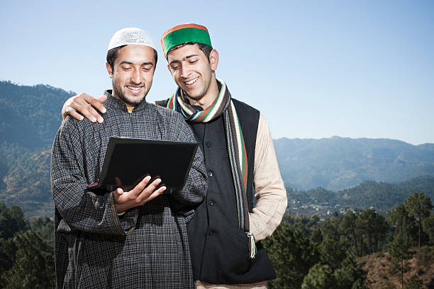 tow happy friends from different cultures of india using laptop. - hinduism stock photos and pictures