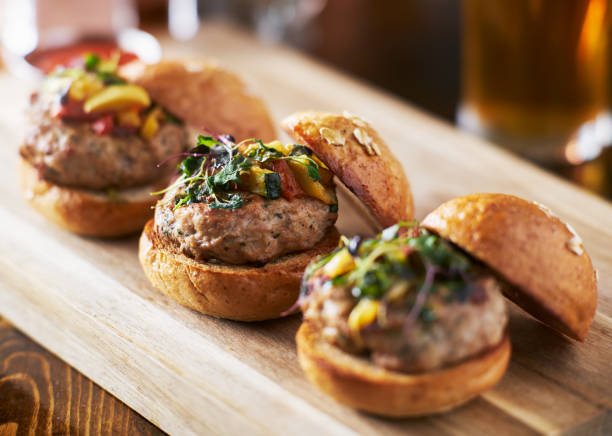 tow of three mini turkey burger sliders with brioche buns tow of three mini turkey burger sliders with brioche buns shot with selective focus slider burger stock pictures, royalty-free photos & images