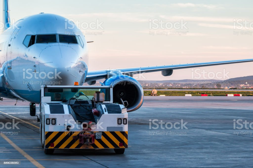 Tow tractor is pushing the passenger airplane стоковое фото