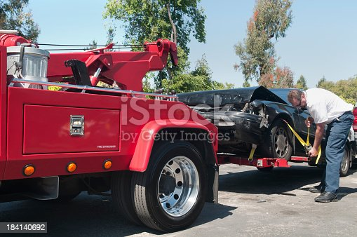 Tow truck driver securely strapping a wrecked car in preparation for towing it.